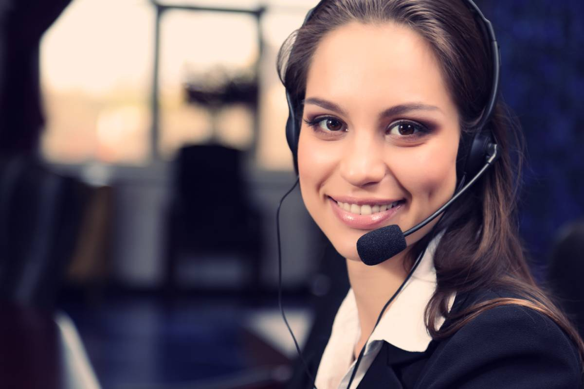A brunette woman wearing a headset smiling