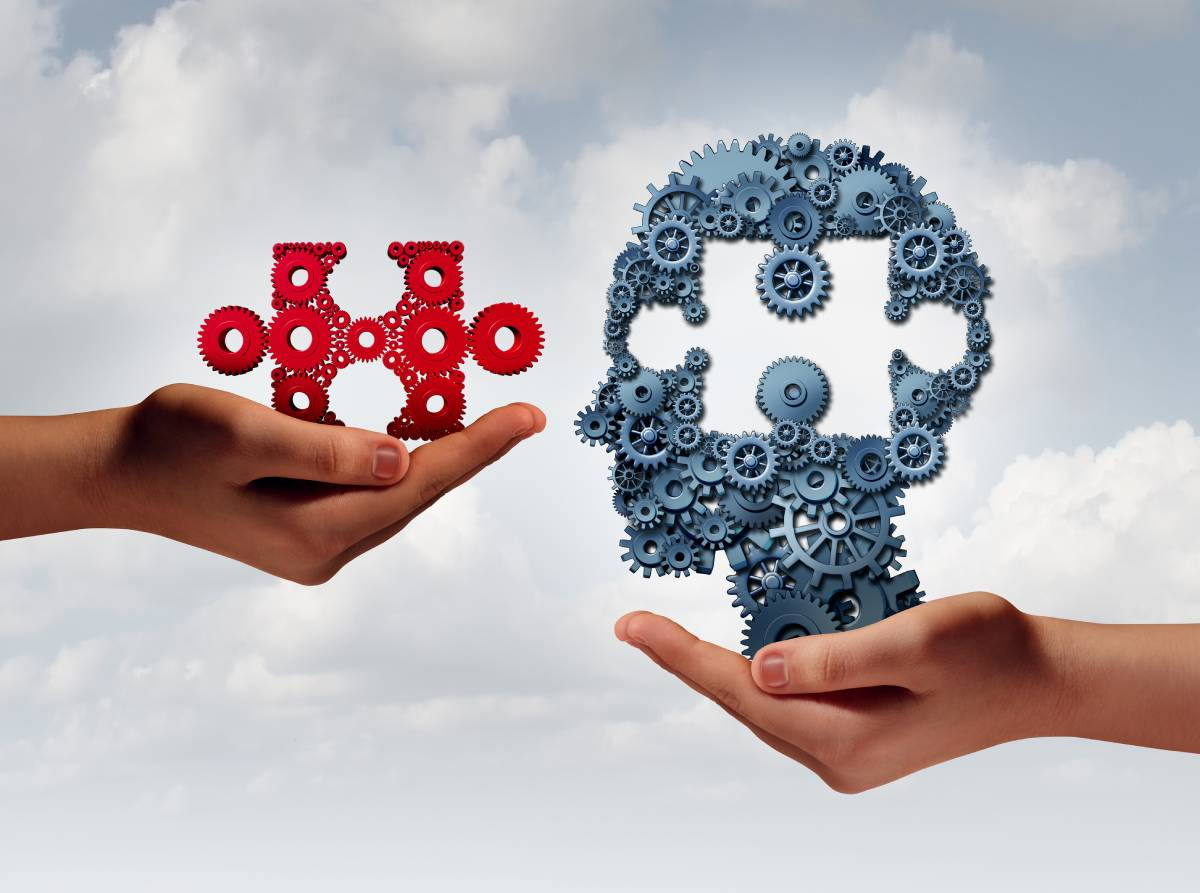 A hand holding a red puzzle piece and another hand holding a gray head with a section missing in the shape of the red puzzle piece