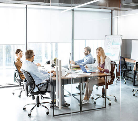 Business People Seated Around Meeting Table in Modern Office