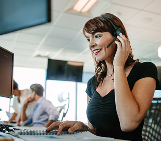 Smiling Woman Wearing Headset at Desk